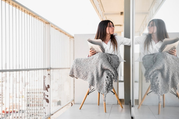Jeune femme, s'asseoir chaise, sur, balcon, journal lisant