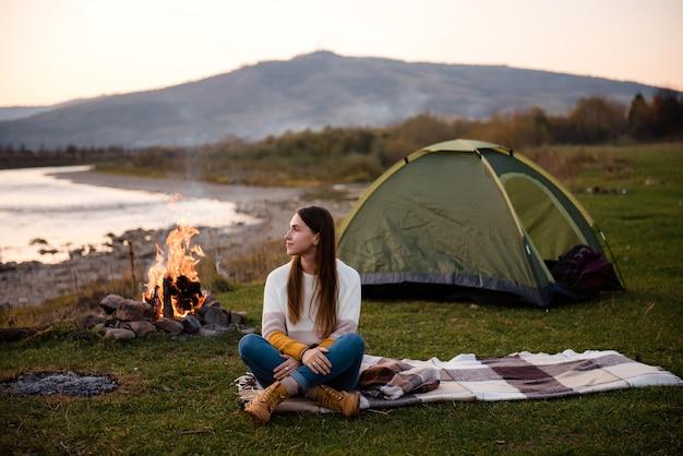La jeune femme s'assied sur une couverture sur l'herbe près de la tente verte et du feu de joie