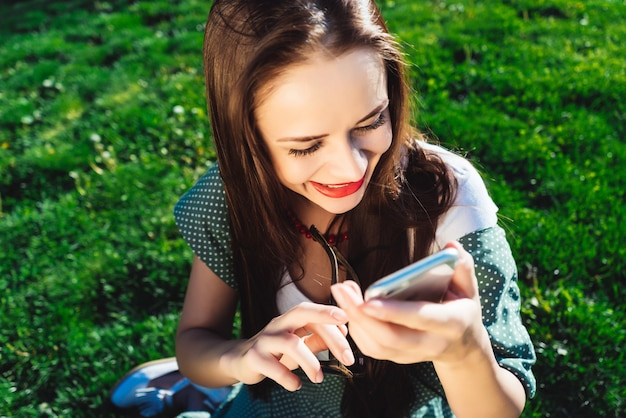 La jeune femme s'assied sur la pelouse avec l'herbe verte lumineuse, rit, imprime quelque chose au téléphone