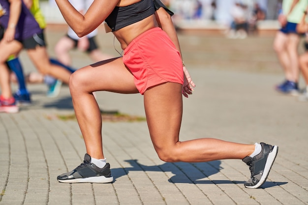 Jeune femme s'échauffant avant d'exécuter le marathon