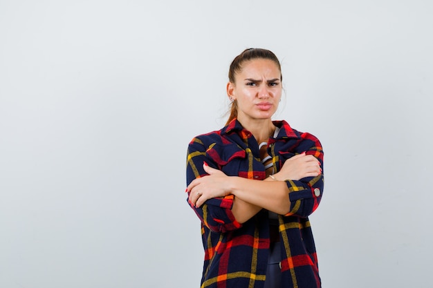 Jeune femme s'embrassant en haut, chemise à carreaux et l'air déçue. vue de face.