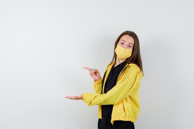 Jeune femme s'étendant la main comme elle tient quelque chose