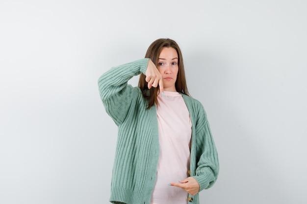 Jeune femme s'étendant la main comme si elle tenait quelque chose