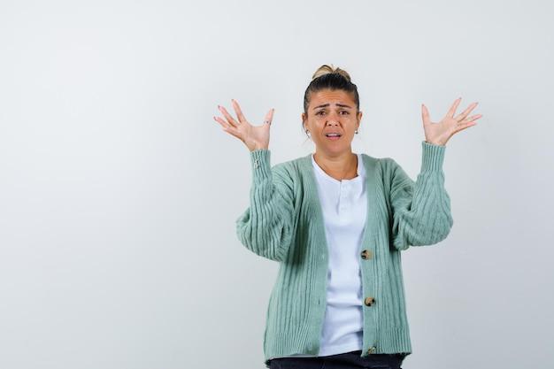 Jeune femme s'étendant les mains comme tenant quelque chose en t-shirt blanc et cardigan vert menthe et à l'air ennuyé