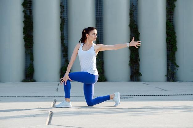 Jeune femme s'étendant sur un pavage en béton faisant des torsions debout sur un genou