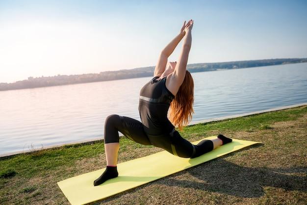 Jeune femme s'étirant les jambes tôt le matin avant le temps de travail en plein air