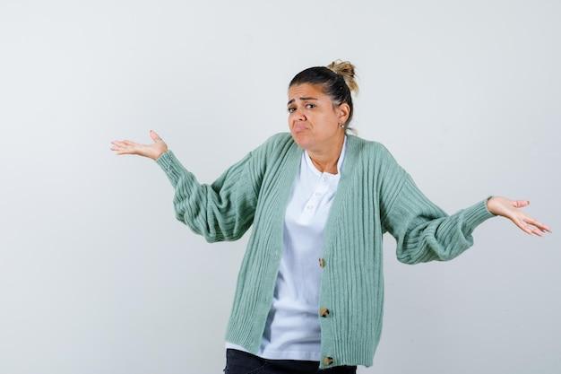 Jeune femme s'étirant les mains de manière interrogative en chemise blanche et cardigan vert menthe et à la perplexité