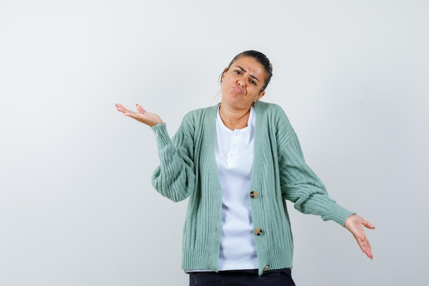 Jeune femme s'étirant les mains de manière interrogative en t-shirt blanc et cardigan vert menthe et à la perplexité