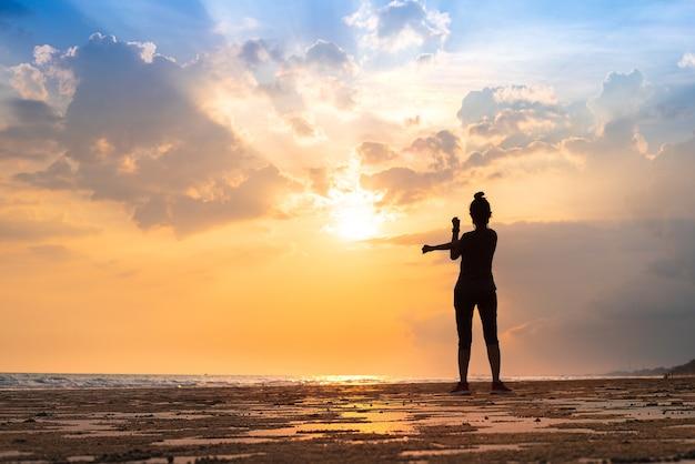 Jeune femme s'étirant pour détendre son corps après une course de jogging et une activité physique pour une bonne santé sur la plage et la mer au beau coucher de soleil et ciel en soirée