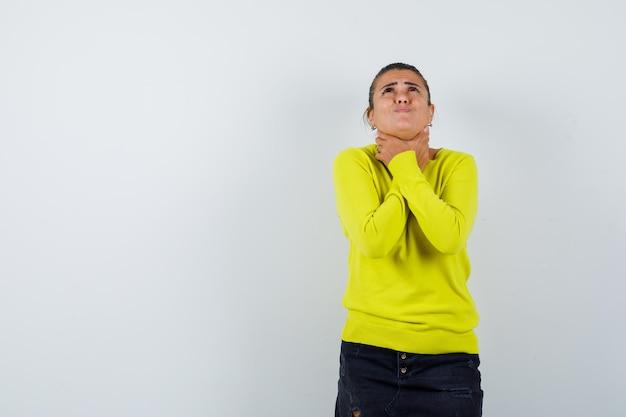 Jeune femme s'étouffant dans un pull, une jupe en jean et l'air désespéré