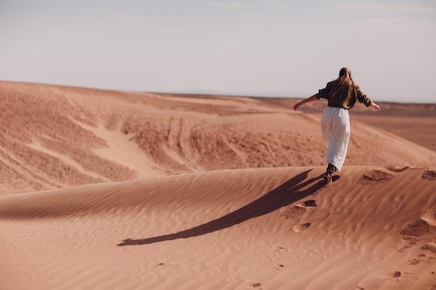 Jeune femme s'exécute sur des dunes de sable dans le désert du sahara