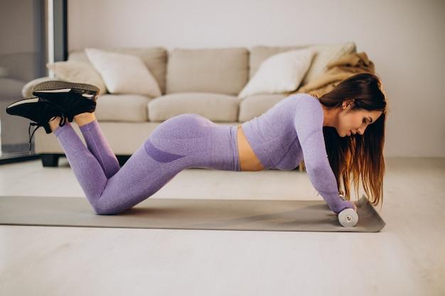 Jeune femme s'exerçant avec des haltères à la maison sur le tapis