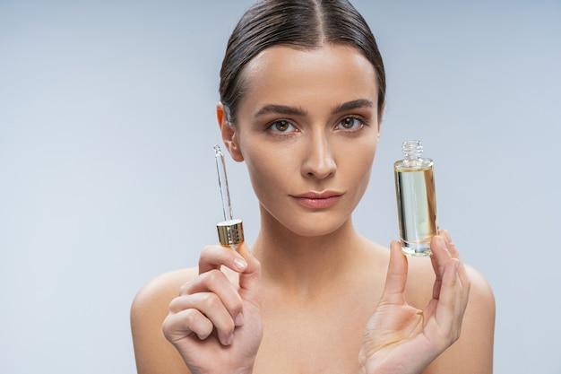 Jeune femme s'occupant de la peau avec du sérum