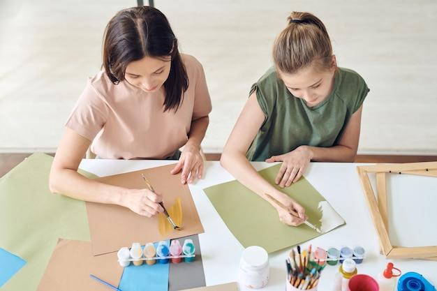 Jeune femme et sa fille adolescente avec des pinceaux peignant à l'aquarelle ou à la gouache sur papier alors qu'elle était assise à son bureau à la maison