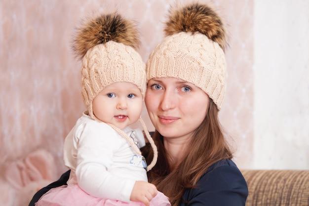 Une jeune femme avec sa fille dans les mêmes casquettes tricotées