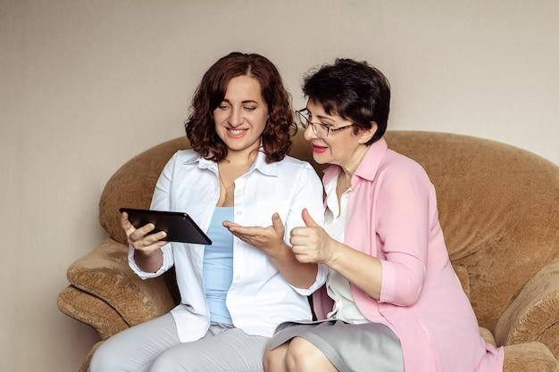 Une jeune femme et sa mère, 60 ans, communiquent sur la tablette par communication vidéo.