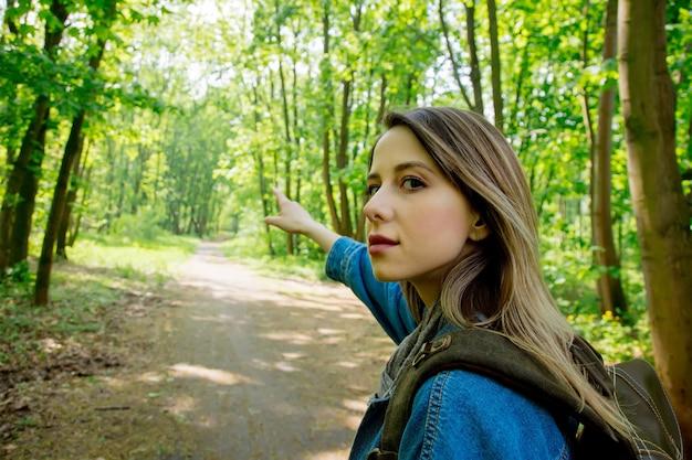 Jeune femme avec sac à dos dans une forêt mixte beskidy en pologne au printemps.