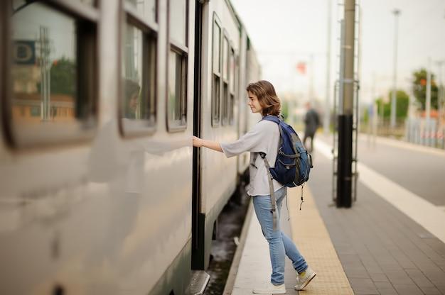 Jeune femme avec sac à dos prendre le train