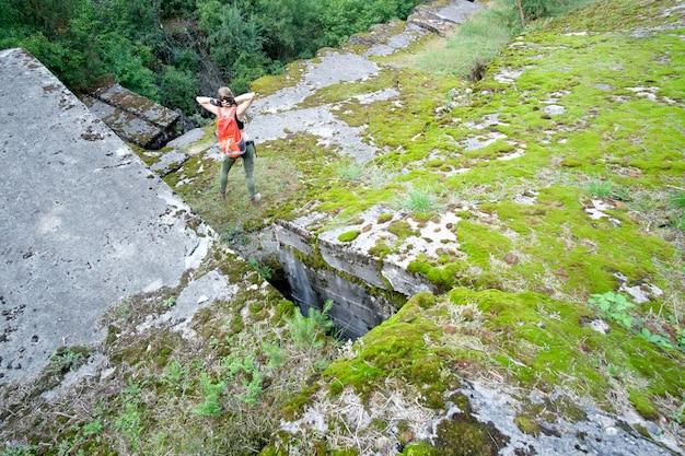 Jeune femme avec sac à dos de voyage orange explore l'ancienne forteresse