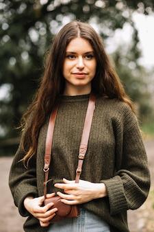 Jeune femme avec un sac photo dans la nature