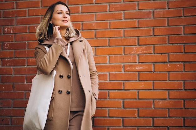 Jeune femme avec un sac près du mur de briques
