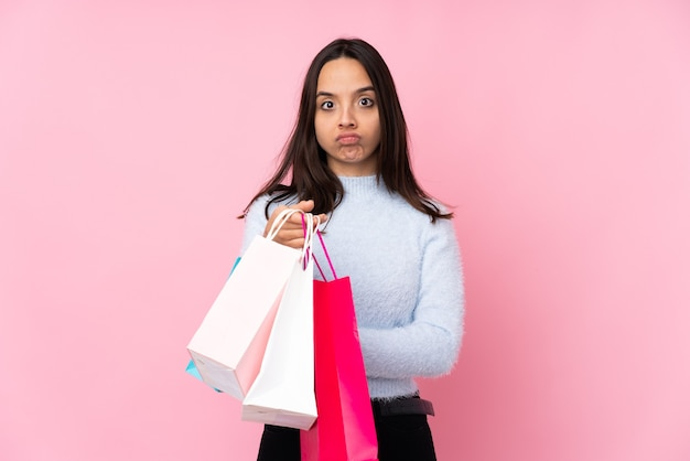 Jeune femme avec sac à provisions fond rose isolé se sentir bouleversé