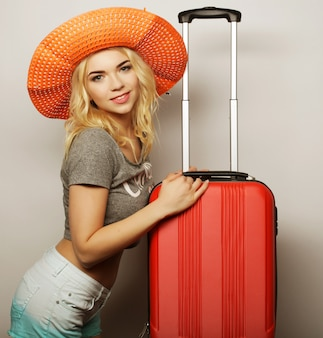 Jeune femme avec un sac de voyage orange
