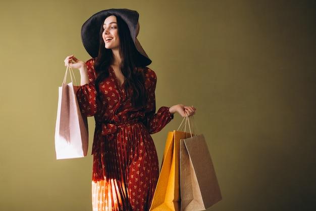 Jeune femme avec des sacs dans une belle robe et un chapeau