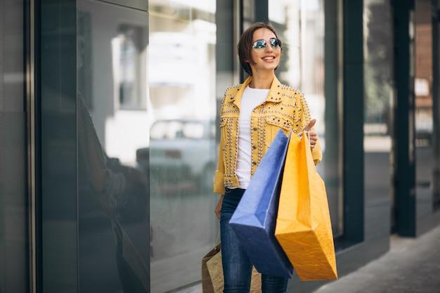 Jeune femme avec des sacs dans la ville
