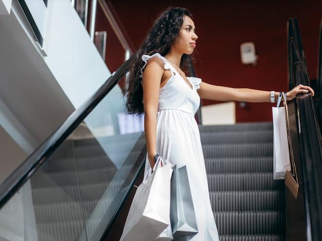 Jeune femme avec des sacs sur un escalator