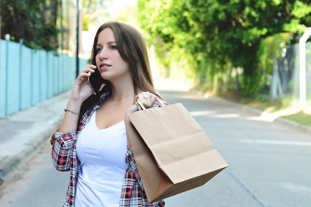 Jeune femme avec des sacs à provisions à l'aide de smartphone