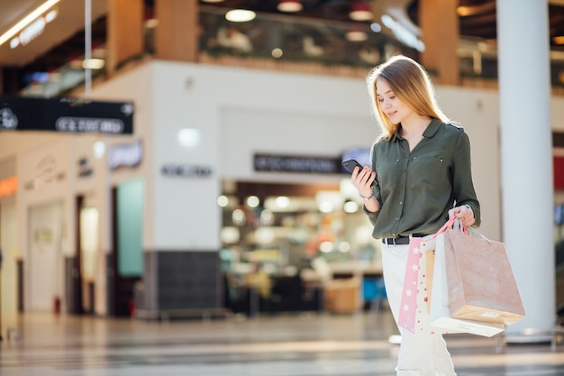 Jeune femme avec des sacs à provisions à l'aide de son téléphone intelligent pour acheter