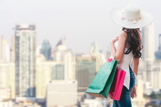 Jeune femme avec des sacs à provisions en faisant du shopping