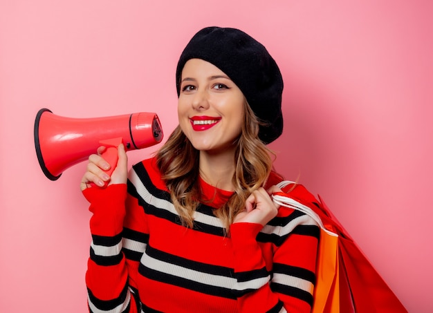 Jeune femme avec des sacs à provisions et haut-parleur sur mur rose