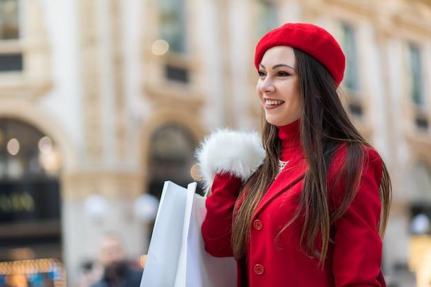 Jeune femme avec des sacs à provisions à milan, italie