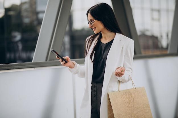 Jeune femme avec des sacs à provisions parlant au téléphone