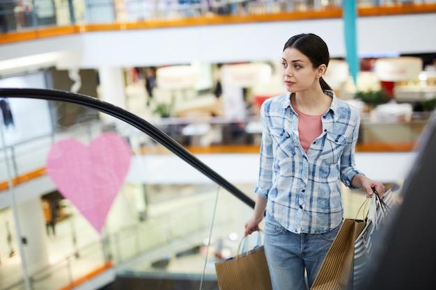 Jeune femme avec des sacs à provisions remontant l'escalator