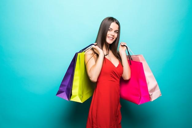 Jeune femme avec des sacs à provisions en robe rouge sur mur bleu
