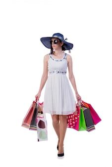 Jeune femme avec des sacs de shopping de noël sur blanc