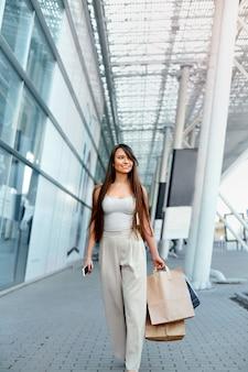 Jeune femme avec des sacs en sortant de la boutique