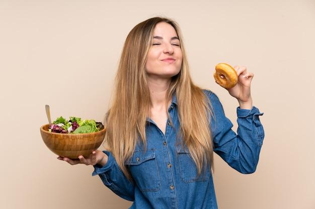 Jeune femme avec une salade sur fond isolé et tenant un beignet