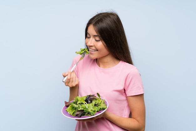 Jeune femme avec une salade sur un mur bleu isolé