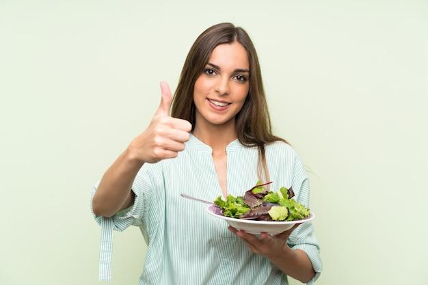 Jeune femme avec une salade sur un mur vert isolé avec le pouce levé parce que quelque chose de bien est arrivé