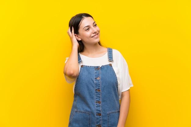 Jeune femme en salopette pensant une idée