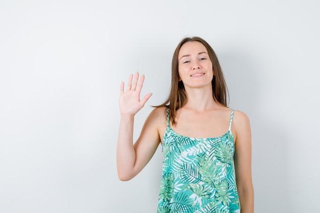 Jeune femme saluant la main ouverte et semblant joyeuse. vue de face.