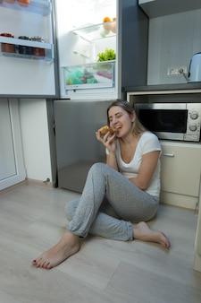 Jeune femme sans sommeil assise sur le sol de la cuisine et mangeant de la pizza