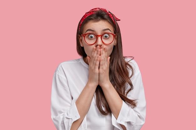 Jeune femme sans voix regarde avec étonnement, couvre la bouche avec les deux mains, a l'air perplexe, porte des lunettes, un bandeau et une chemise blanche