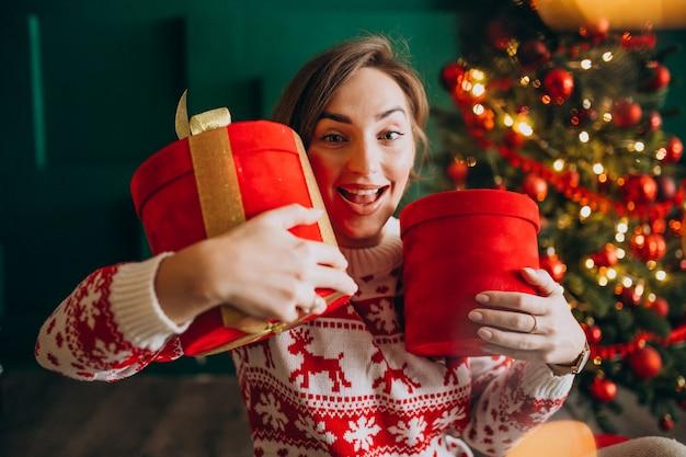 Jeune femme avec sapin de noël tenant des boîtes rouges