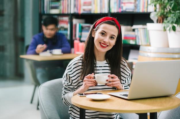 Jeune femme satisfaite assise à la petite table ronde avec un ordinateur portable dessus et tenant une tasse