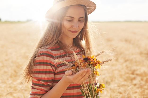 Jeune femme satisfaite positive portant une robe dépouillée et un chapeau de paille, posant dans un champ de blé, tenant un bouquet, le touchant soigneusement, profitant d'une journée ensoleillée d'été, ayant une expression faciale agréable.